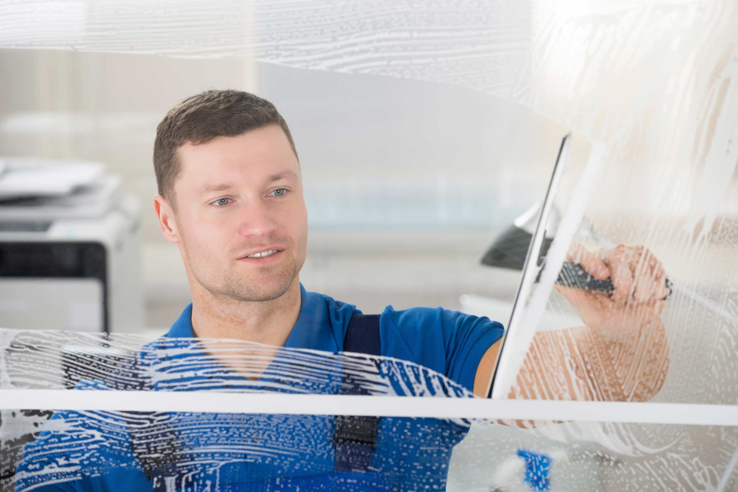 employee cleaning a window